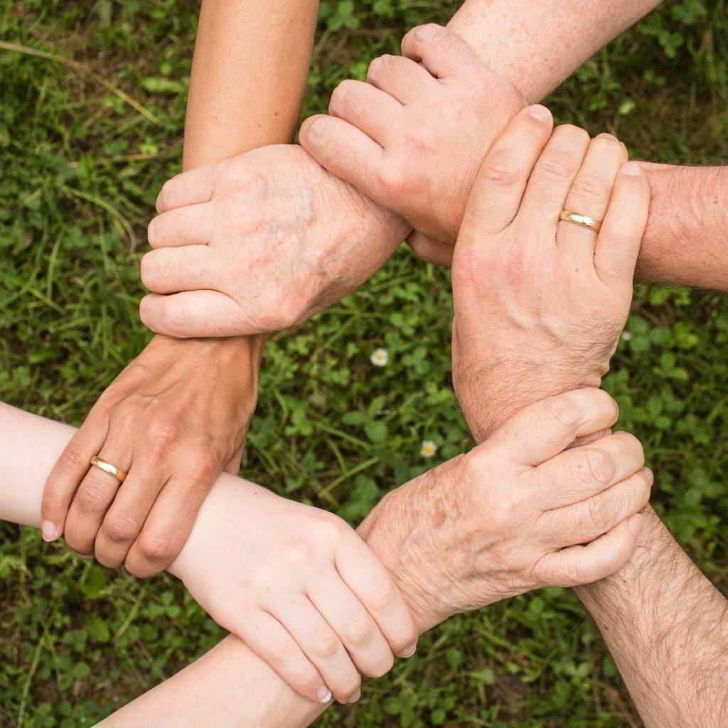 sechs Hände, die sich gegenseitig greifen